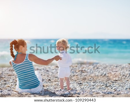 Mother spending time with baby on beach - stock photo