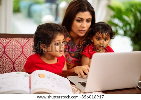 Mother spending time with her two children, focus on little girl - stock photo