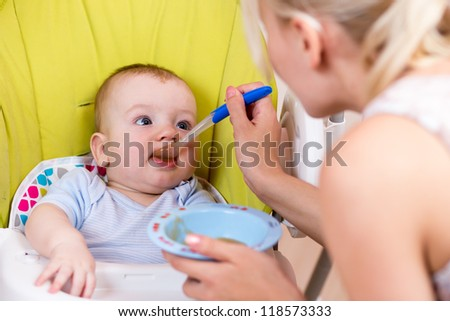 mother spoon feeding her baby boy - stock photo