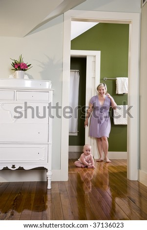 Mother standing beside chubby baby sitting on wood floor - stock photo