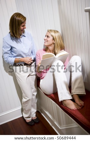 Mother standing beside teenage daughter reading book at home - stock photo