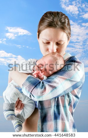 mother stands and holds the baby - stock photo