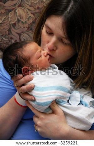 Mother still at the birthing center, loving on her newborn baby. - stock photo