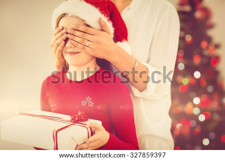 Mother surprising her daughter with christmas gift at home in the living room - stock photo