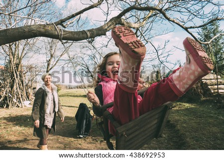 Mother swaying her daughter on a swing - stock photo