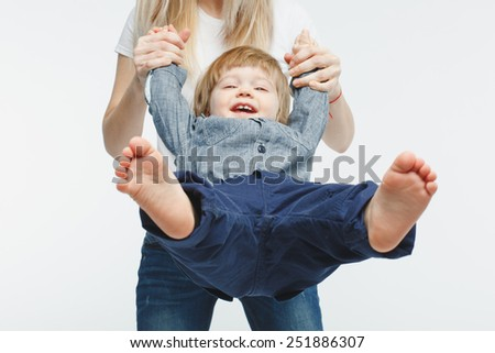 mother swinging her one year old baby over white background - stock photo