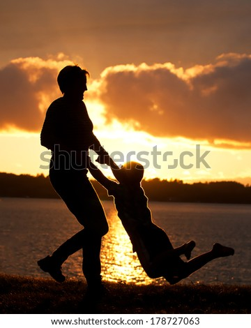 Mother Swings Young Son Silhouette Lake Background - stock photo