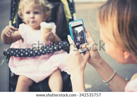 Mother takes a photo of her daughter eating ice-cream during a walk outdoors. Toned image - stock photo