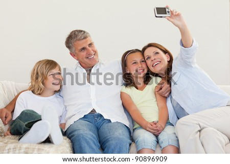 Mother taking a family picture on the couch - stock photo