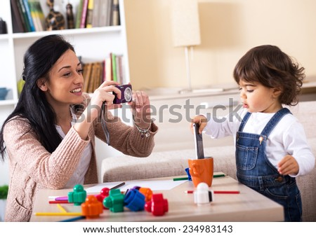 Mother taking a picture of her baby girl.They playing with toys in living room. - stock photo