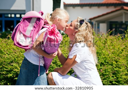Mother taking her daughter to school, saying her goodbye for the day - stock photo