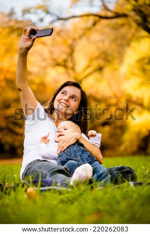 Mother taking picture of her and baby with smartphone camera - stock photo