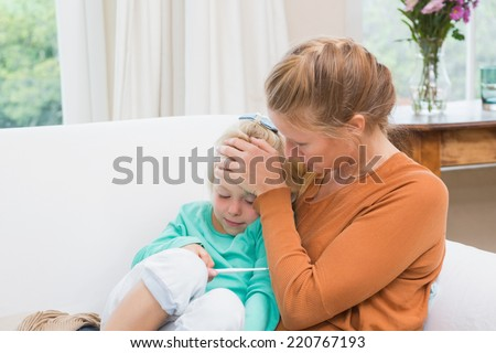 Mother taking the temperature of sick daughter at home in the living room - stock photo