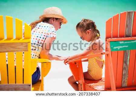 Mother talking to upset little daughter while sitting on colorful wooden chairs at tropical beach during summer vacation - stock photo