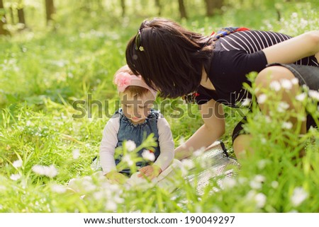 mother talking with her cute daughter in grass - stock photo