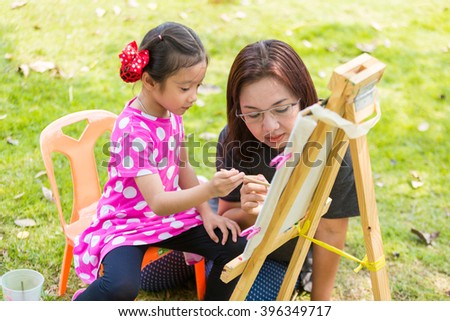 Mother teach daughter painting with easel in garden - stock photo