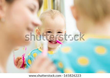 mother teaches baby brushing teeth - stock photo