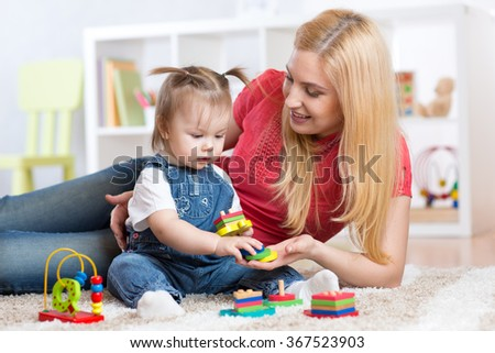 Mother teaches her child to distinguish shape and colur plaing with toys. - stock photo