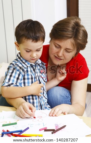 Mother teaches her son to draw - stock photo