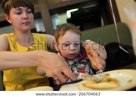 Mother teaches her son to use cutlery in the restaurant - stock photo