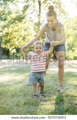 Mother teaches his son how to walk - stock photo