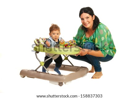 Mother teaching baby in walker in their home - stock photo