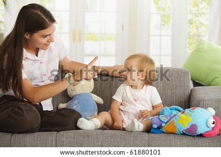 Mother teaching babygirl sitting on sofa at home, smiling.? - stock photo