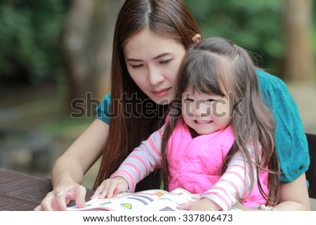 Mother teaching children reading a book - stock photo