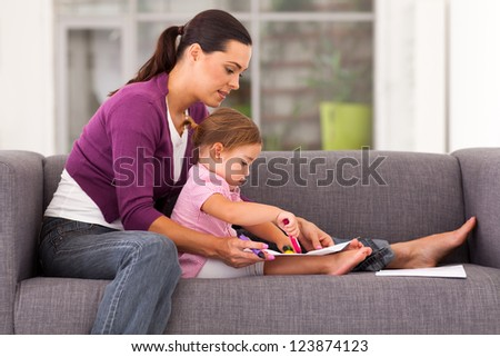 mother teaching daughter drawing on sofa at home - stock photo