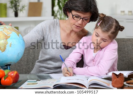 Mother teaching daughter from home - stock photo