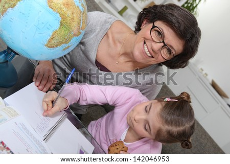 Mother teaching daughter geography - stock photo