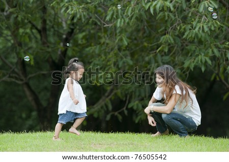 Mother teaching daughter learned a little walk in the park. - stock photo