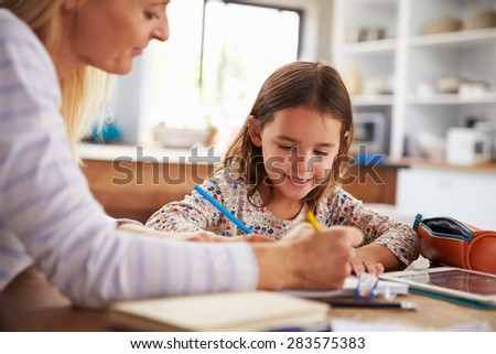 Mother teaching her daughter at home - stock photo