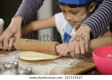 Mother teaching her daughter making bread with rolling pin on the kitchen - stock photo