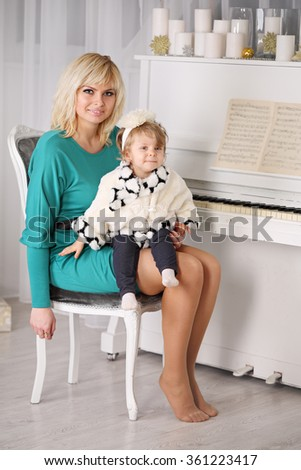 Mother teaching her daughter to play piano - stock photo