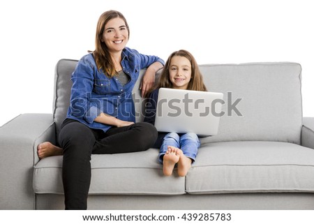 Mother teaching her little daughter working with a laptop - stock photo