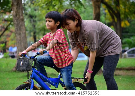 Mother teaching her son cycling - stock photo