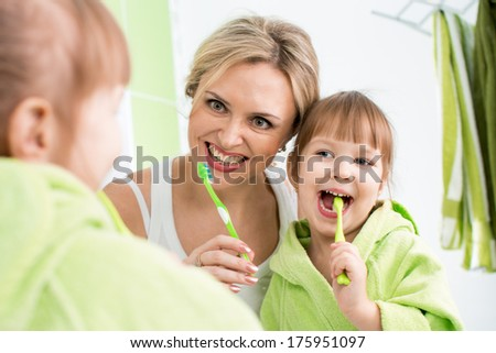 mother teaching kid teeth brushing - stock photo