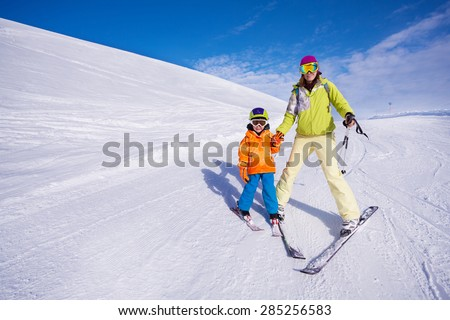 Mother teaching little boy 4 years old how to mountain ski going on the piste on resort - stock photo