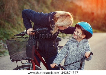 Mother teaching son cycling at outdoor in sunset - stock photo