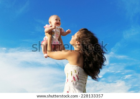 Mother throws up laughing baby over blue sky, outdoor portrait. - stock photo