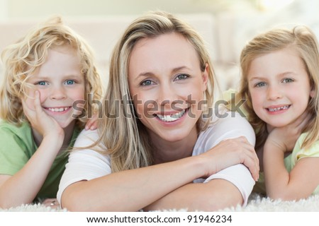 Mother together with her children on the floor - stock photo
