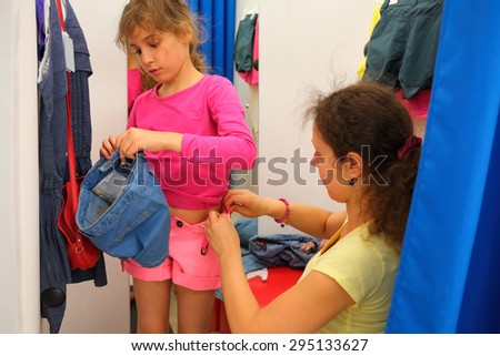 Mother tries daughter shorts in dressing room of clothing store