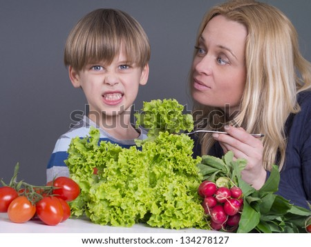 mother trying to feed a boy who dislikes fresh salad - stock photo