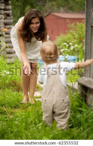 Mother urges a small sonny to make the first steps - stock photo