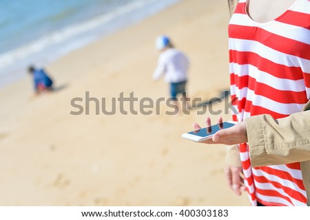 Mother using cellular smartphone on the outside beach sandy background, sunny day - stock photo