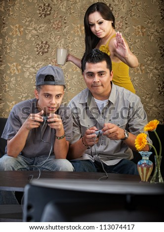 Mother vying for attention from husband and son playing video games - stock photo