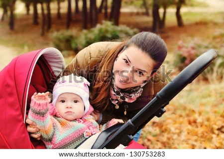 mother walking in the park with her baby in stroller - stock photo