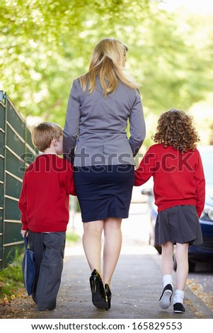 Mother Walking To School With Children On Way To Work - stock photo