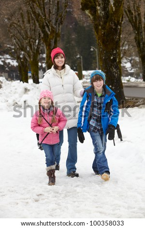 Mother Walking Two Children To School Along Snowy Street In Ski Resort - stock photo